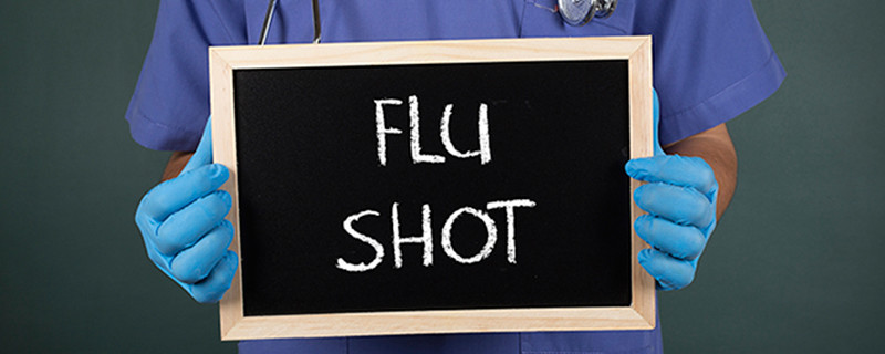 health professionl with gloves holding a chalkboard with the text flu shot written on it