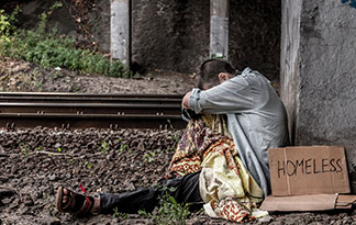 Person sitting next to railroad tracks with a cardboard sign that says, 'Homeless'