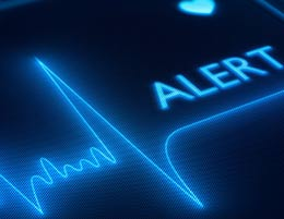 A heart monitoring machine with the word 'ALERT' on it.