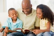 Picture of a father reading to his son and daughter.