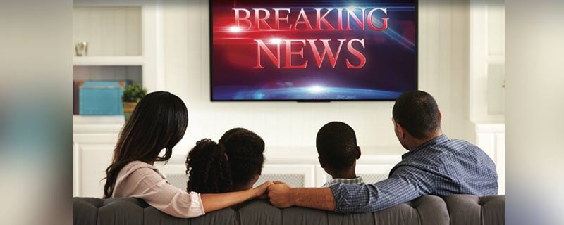 Family watching breaking news alert on television